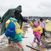 A family of refugees trying to cross the muddy field at the transit camp of Idomeni, Greece. <br /> <br /> Thousands of refugees are stranded in Idomeni unable to cross the border. The facilities are stretched to the limit and the conditions are appalling.