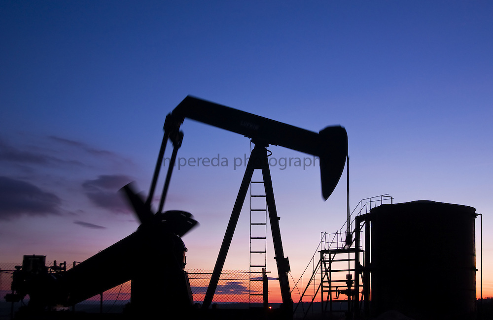 Oil pumping station on the horizon at sunset in Ayoluengo´s Oil Field (Burgos)
