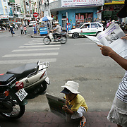 A decade ago Vietnams roads were teaming with bicycles. But as the countries economic growth increased bringing relative affluence to the working class, the push bike has been replaced by the scooter as the main mode of transport for the nations population.. Ho Chi Minh City alone has an estimated three million scooters buzzing around the streets day and night. Everyday life is dominated by the site of the scooter. Street corners have become parking lots for rows upon rows of parked scooters.. Puncture repair workmen wait on every city street to come to the aid of the rider with a blown tyre, and make a quick buck in the process, while families have a night on the town together, all seated on the same scooter!.Any number of items can be seen transported on the back of a scooter, from pigs to wardrobes anything that can be tied down is moved on the trusted scooter..Even in the outlying country areas the scooter is now used to transport produce to and from the markets. While even beach goers at the coastal towns head for a swim and a sunbathe accompanied by their scooter.  Street scene, Ho Chi Minh City, Vietnam on September 29, 2006. Photo Tim Clayton