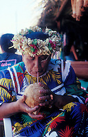 French Polynesia, Islands in the South Pacific, part of the French overseas Territories.Photo by Owen Franken.traditionally dressed woman drinking coconut milk in the Papaeete Market.Photo by Owen Franken