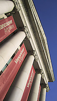 Red banners between Ionic columns, Vancouver Art Gallery, Vancouver BC; framed by blue sky