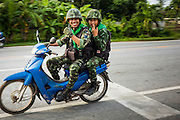 11 JULY 2013 - PATTANI, PATTANI, THAILAND:   Thai soldiers patrol a highway in Pattani province. More than 5,000 people have died in violence since 2004 when Muslim insurgents restarted an insurgency against the Thai government. Thai soldiers frequently use motorcycles, pickup trucks and other soft sided vehicles for patrols.     PHOTO BY JACK KURTZ