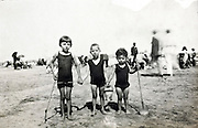 three children posing while playing on the beach early 1900s