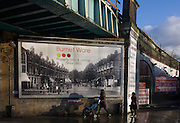 Property estate agent's billboard showing old street scene under railway bridge in Herne Hill, South London SE24.