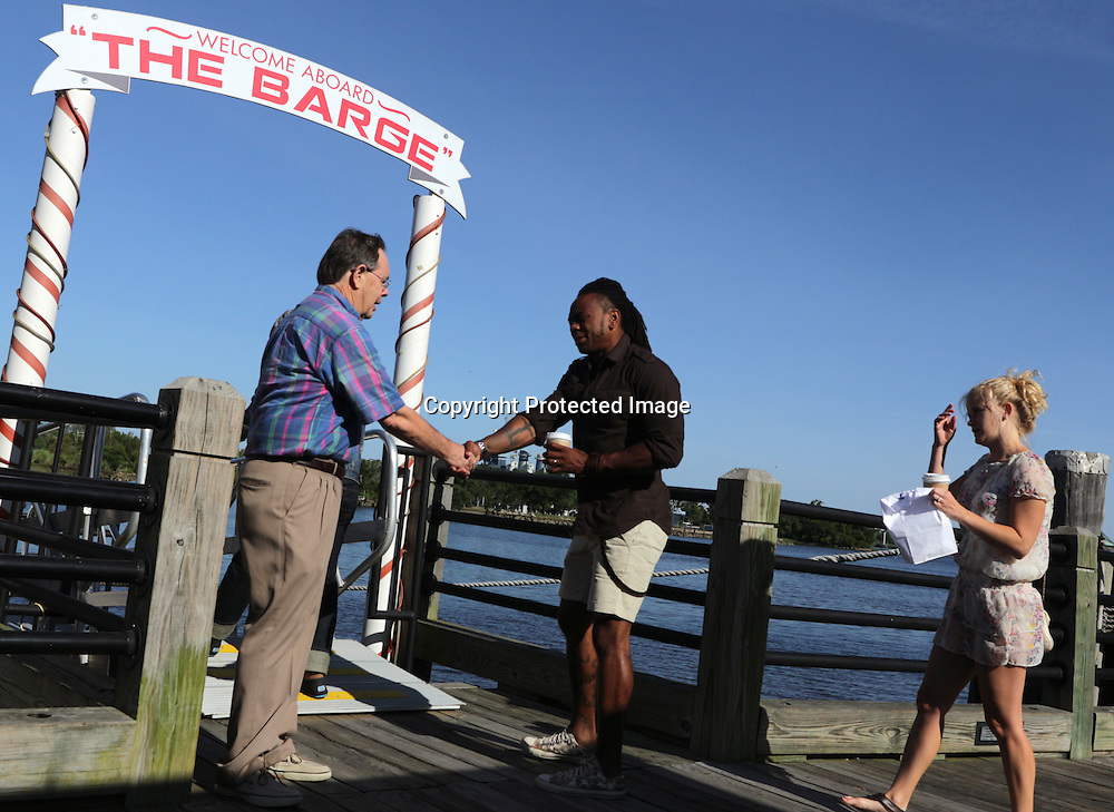 Ben Fussell, left greets T.J. Dunn and Libby Dunn as they arrive for church service at The Anchor Sunday June 1, 2014 on the Wilmington, N.C. waterfront. (Jason A. Frizzelle)