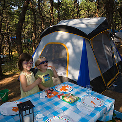 A sister and brother (ages 2 and 4) enjoying a snack at their campsite at the North of Highland Campground near the Cape Cod National Seashore in Truro, Massachusetts.