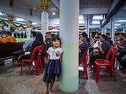 20 AUGUST 2015  - BANGKOK, THAILAND: A girl leans against a pillar in the temple at the funeral for Yutnarong Singraw Thursday. More than 100 people gathered at Wat Bang Na Nok in Bangkok for the third day of the funeral rites for  Yutnarong Singraw, a Thai man who was killed in the bombing at the Erawan Shrine in Bangkok Monday. Yutnarong was delivering legal documents when the blast occurred. More than 20 people were killed and more than 100 injured in the blast.    PHOTO BY JACK KURTZ