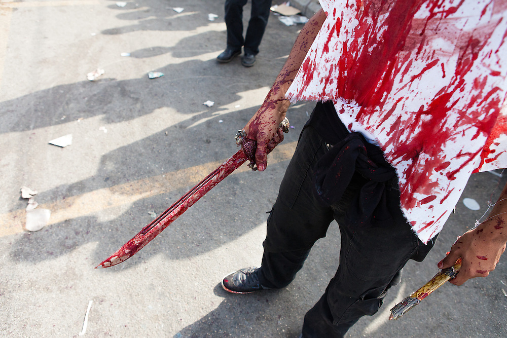 A shiite muslim man, carrying a traditional sword and knife, covered in his own blood, during the commemoration of the Day of Ashura in Nabatieh, Lebanon.