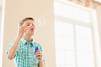 Boy blowing bubbles at home