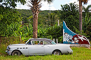 Old Buick by a sign of Mella, Camilo, and Che in near San Andres, Holguin Province, Cuba.