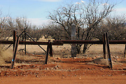 Holes have been cut in the fence at the Mexican border that divides Sonora with Lochiel, Arizona, USA, a former official port-of-entry.  A concrete post originally indicated the international boundary.