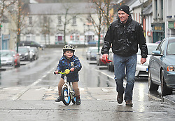 Pedal Power its all in his stride. Despite the Wet Conditions Tomas Cadden aged 4 pictured with Daddy Tommy taking part in the the Streets of Westport New Year's Day 5km Resolution Run around the town.<br /> Pic Conor McKeown