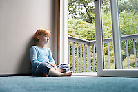 Young girl (5-6) sitting cross-legged on carpet looking through balcony door