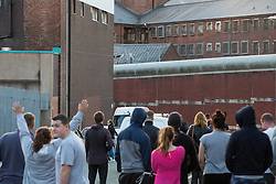 © Licensed to London News Pictures . 13/09/2015. Manchester, UK. Crowds watch as an inmate at HMP Manchester ( Strangeways Prison ) , named as STUART HORNER , climbs netting and protests conditions inside . Photo credit : Joel Goodman/LNP
