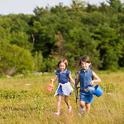 Young girls walk through a field of lowbush blueberries in Alton, New Hampshire.