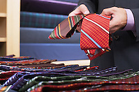 Businessman selecting ties in clothes store mid section