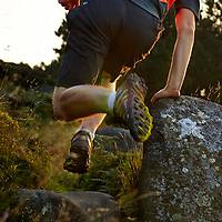 A photograph of a fell runner jumping over rocks on ilkley moor at sunset