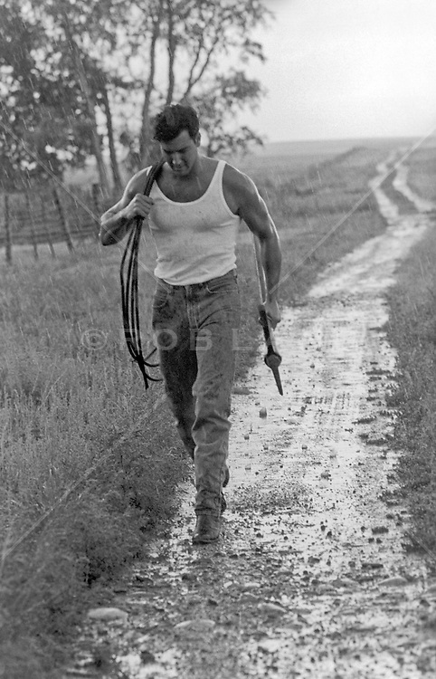 rugged ranch hand walking down a dirt road in the rain