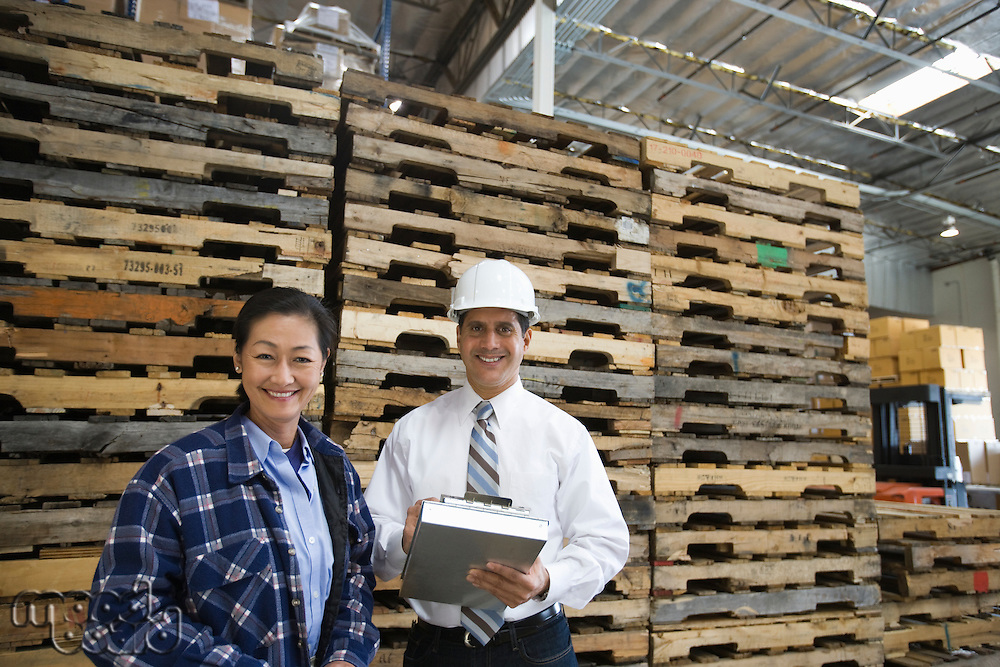 Woman and man standing in distribution warehouse portrait