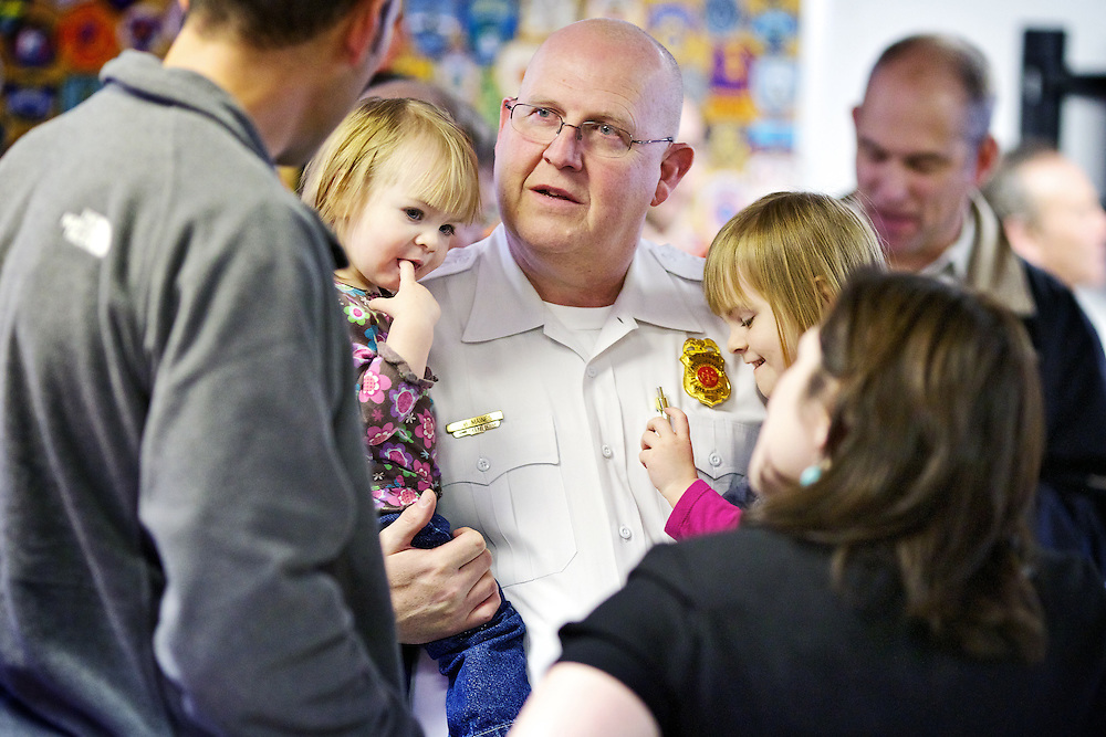 Bob Maines, the chief of training for Northern Lakes Fire Protection District, holds his granddaughters Sophie, 18 months, left, and Abi, 4, during his retirement party Friday in Hayden. Maines retired from Northern Lakes Fire following a 30 year career in the fire service.
