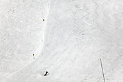 one person on a large slope skiing down hill