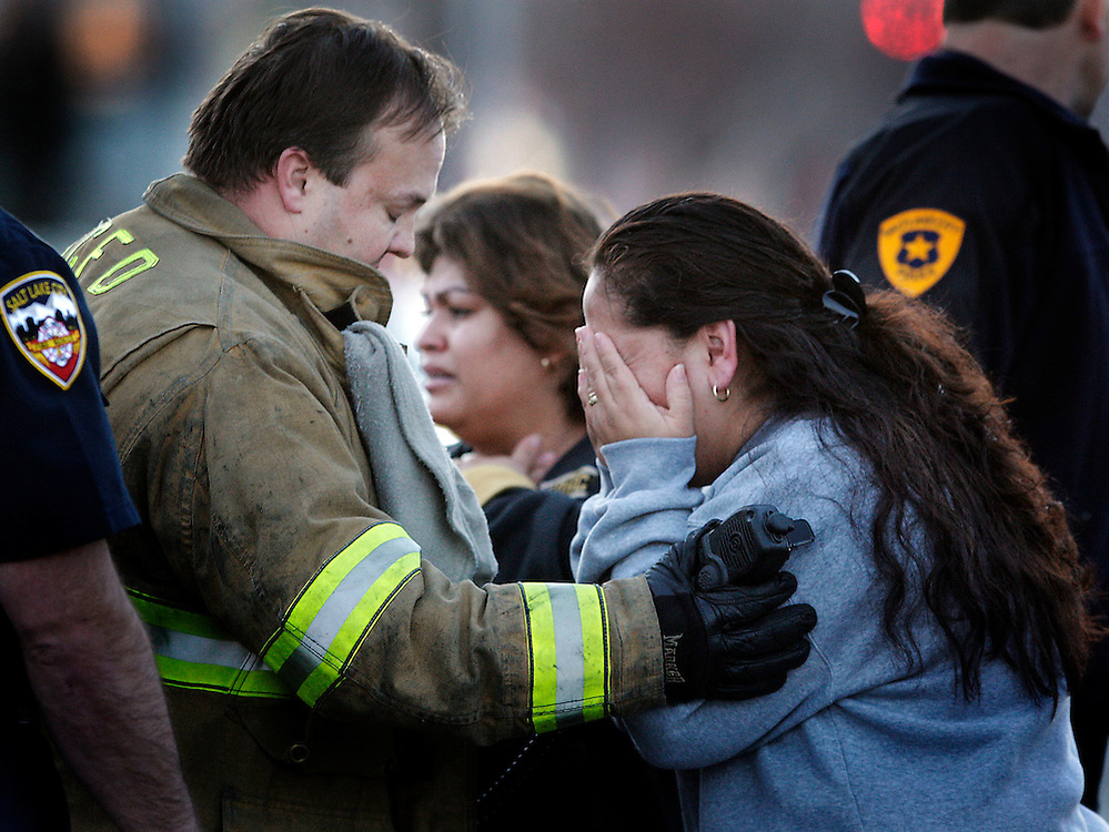 A fireman consoles a relative of one of the victims of a shooting in the Sears parking lot at about 748 south State street react to a shooting which let one person dead and another in critical condition in Salt Lake City, Utah Sunday, Jan. 6, 2007.  August Miller/ Deseret Morning News .