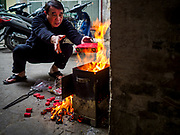 "22 DECEMBER 2017 - HANOI, VIETNAM: A man burns ""ghost money"" near his home in the old quarter of Hanoi. The old quarter is the heart of Hanoi, with narrow streets and lots of small shops but it's being ""gentrified"" because of tourism and some of the shops are being turned into hotels and cafes for tourists and wealthy Vietnamese.    PHOTO BY JACK KURTZ"