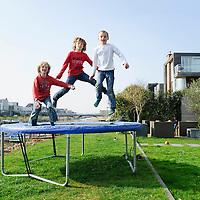Nederland Amsterdam 29 maart 2011 20110329 Nieuwbouwwijk Ijburg, kinderen spelen, zij springen op een trampoline, in de achtertuin van een van de grote woningen met individuele architectuur die aan het water grenzen. Individueel vormgegeven architectuur. Noot: Fotograaf heeft toestemming gekregen van volwassene op de achtergrond om de beelden te maken.  , nieuwbouwhuizen, nieuwbouwwijk, nieuwbouwwoning, nieuwbouwwoningen, nieuwe, nieuwe wijk, onbezorgd, onroerend goed, onroerende goederen, ontspannend, ontspannende activiteit, ontspanning, ontwikkelen, ontwikkeling, op gewicht blijven, opgroeien, ozb, people, people and lifestyle, personen, persoon, Playing, plezier hebben  blij, property, ravotten, recreatie, Recreation, recreeren, relax, relaxed, relaxen, relaxing, ruime tuin, ruimtelijk, ruimtelijke omgeving, samen, samen leven, samen spelen, samen wonen, samenleven, sociaal gedrag, sociale, sociale banden, sociale cohesie, sociale samenhang, socialisering, socialising, spare time, speel plek lokatie, speellokatie, speelplaats, speelplek, speelplekken, speelruimte, speels, speelse, spelen, spelende, spelenderwijs, sportief, sportieve, sportive, springen, sprong, stadsdeel,  Foto: David Rozing