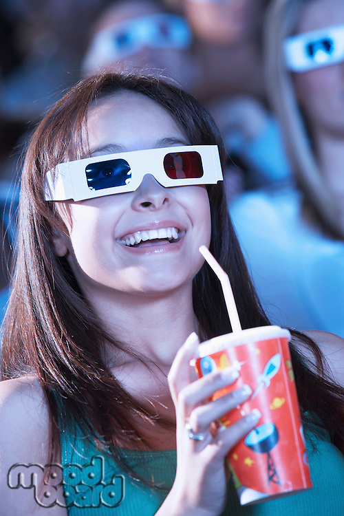 Young woman wearing 3-D glasses watching 3-D movie in theatre drinking soft drink