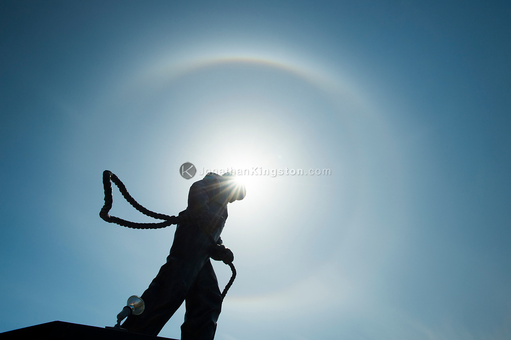 Low angle view of a statue of a fisherman surrounded by a sun dog (parhelion) in Petersburg, Alaska.