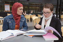 Two students; working together outside,