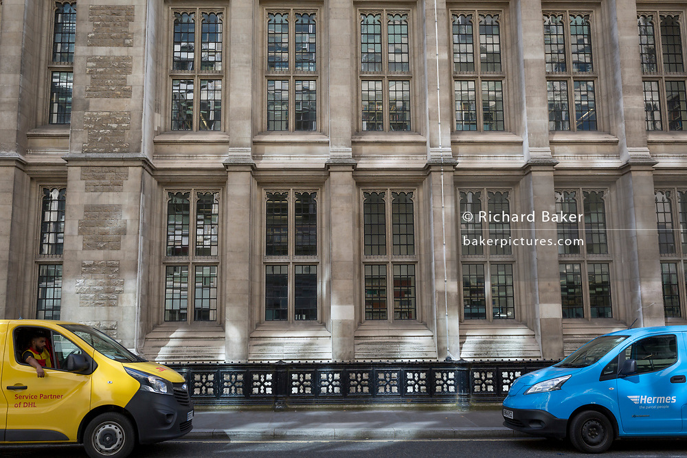 DHL and Hermes vans are parked facing each other outside the Maugan Library off New Fetter Lane in the City of London, on 22nd August 2019, in London, England.