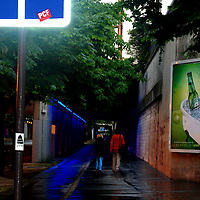 Two women walking along a rainy street in Paris with blue pedestrian sign in foreground.  Taken in 2009 wiht a DSLR Nikon D80.