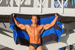 handsome All American man in great shape showing off his muscles while holding up a large towel by a lifeguard stand in Miami Beach, Florida