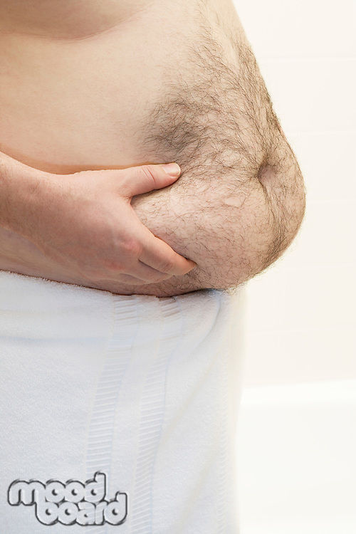 Barechested man with hands on belly mid section
