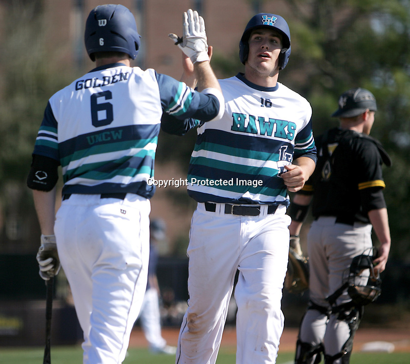 UNCW's Gavin Stupienski is greeted at homeplate by Casey Golden after scoring a run against VCU. (Jason A. Frizzelle)