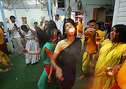 A woman swallows fire as she and fellow Hindu worshippers trance dance at a Temple that honors the Goddess kali, in New York. The worshippers are mostly immigrants from Trinidad whose ancestors left India to work in the Caribbean.