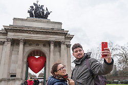 "© Licensed to London News Pictures. 14/02/2018. LONDON, UK. Tourists take a selfie against a giant chubby heart balloon at Wellington Arch as part of ""Chubby Hearts Over London"",  a design project conceived by Anya Hindmarch.  Supported by the Mayor of London, the British Fashion Council and the City of Westminster giant chubby heart balloons will be suspended over (and sometimes squashed within) London landmarks as a declaration of love to the city starting on Valentine's Day and continuing throughout London Fashion Week.   Photo credit: Stephen Chung/LNP"