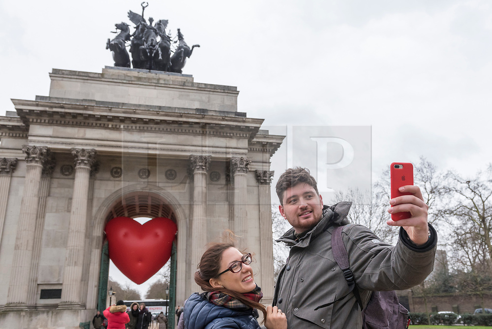 """© Licensed to London News Pictures. 14/02/2018. LONDON, UK. Tourists take a selfie against a giant chubby heart balloon at Wellington Arch as part of """"Chubby Hearts Over London"""",  a design project conceived by Anya Hindmarch.  Supported by the Mayor of London, the British Fashion Council and the City of Westminster giant chubby heart balloons will be suspended over (and sometimes squashed within) London landmarks as a declaration of love to the city starting on Valentine's Day and continuing throughout London Fashion Week.   Photo credit: Stephen Chung/LNP"""