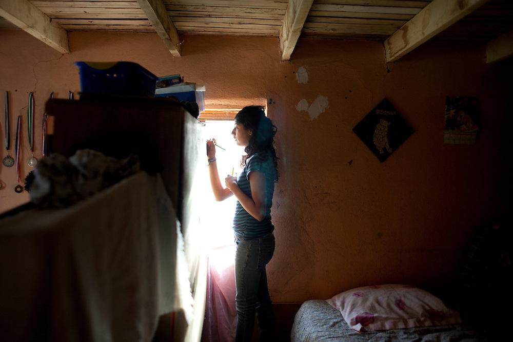 Tania Gonzalez, 15, paints on a friend's dresser in the Diaz Ordaz colonia in Ciudad Juarez, Chihuahua Mexico on April 28, 2010.