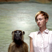 20 something female standing next to guinea baboon taxidermy.