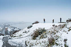 © Licensed to London News Pictures. 10/12/2017. Aberystwyth, UK. People playing in the first snow of the winter at Aberystwyth on the Welsh coast, as the wintry conditions spread of much of the middle of the UK.  People are out  walking on Constitution Hill overlooking the town, making the most of the snowy scenes .Photo credit: Keith Morris/LNP