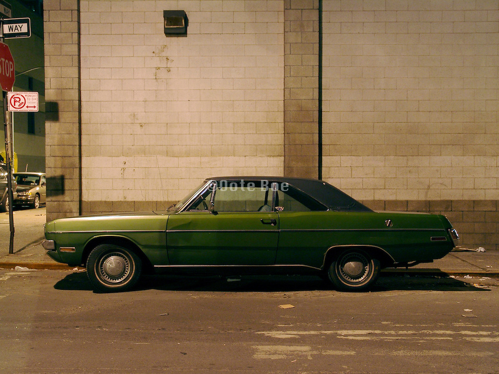 An old Dodge Swinger parked on the corner of a street in a deserted neighborhood.