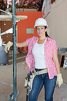 Portrait of young architect wearing hardhat standing at construction site