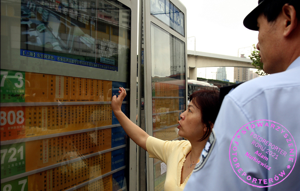 WOMAN ASKING POLICE OFFICER ABOUT BUS SCHEDULE IN THE CENTRE OF SHANGHAI IN CHINA..SEPTEMBER 30, 2007.( PHOTO BY ADAM NURKIEWICZ / MEDIASPORT )..