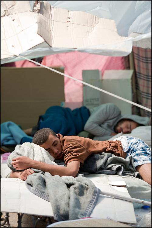 """Des manifestants se reposent dans le camp. // Le mouvement spontane du """"15 M"""" (15 mai) compose de citoyens espagnols campe depuis 2 semaines sur la place Puerta Del Sol avec pour revendication la construction d'une democratie nouvelle. Organise en commission les citoyens prennent la parole lors d'assemblee ouverte a tous - Place Puerta Del Sol à Madrid le Juin 2011. ©Benjamin Girette/IP3Press"""