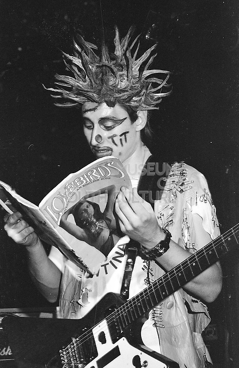 A member of Madhatters reading a magazine on stage, UK, 1980s.