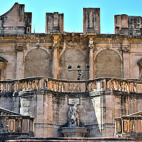 Inside of Monte di Pietà in Messina, Italy<br /> Messina's pawnbroker, who helped imprisoned debtors, began in 1541. Construction of the Palace of the Pawnbroker was started in 1616 but only the first floor was completed.  In 1741 this elegant double staircase designed by Antonino Basile was added. Most of the structure was destroyed during the 1908 earthquake and WWII, leaving only the façade and this open-air courtyard.  Monte di Pietà is now rented out for cultural events yet is also available to tour.