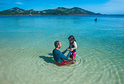 Father plays with his daughter on the clear waters of Nanuya Lailai island, the blue lagoon, Yasawas, Fiji, South Pacific