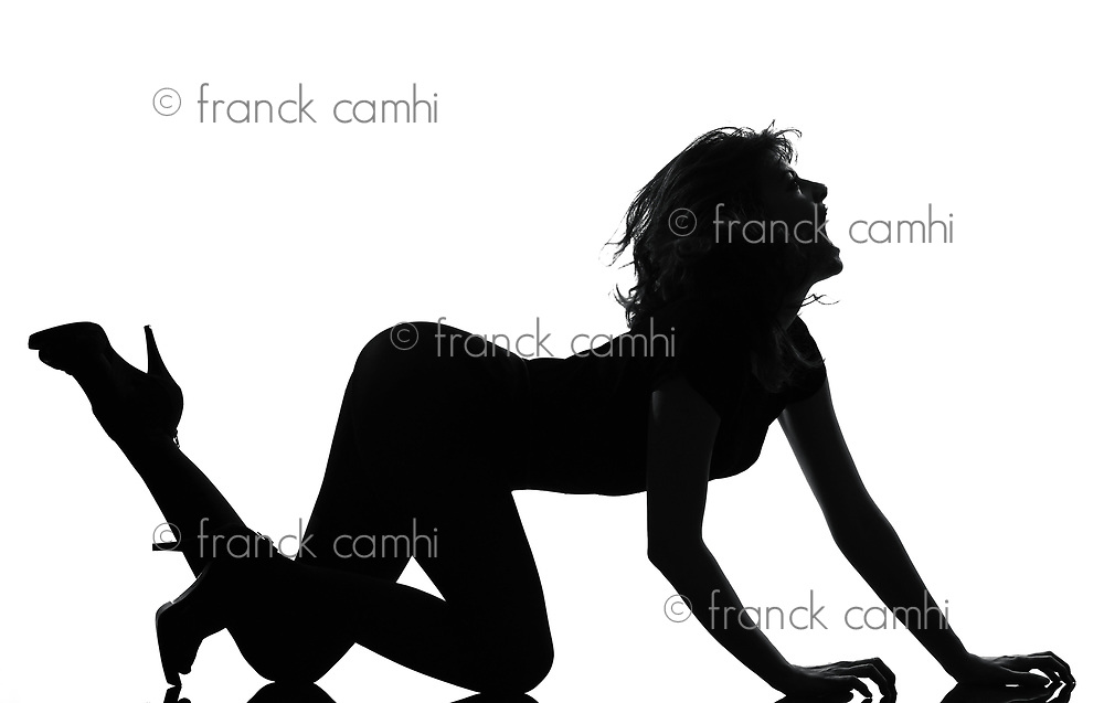 full length silhouette in shadow of a young woman crouching  roar in studio on white background isolated